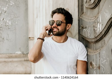 Handsome bearded hispanic man using mobile smartphone for surfing web internet, making call and looking digital city map. Male using electronic device in travel.
