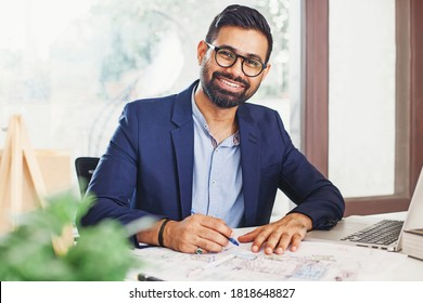 Handsome bearded Indian architect working from home on a building blueprint and laptop