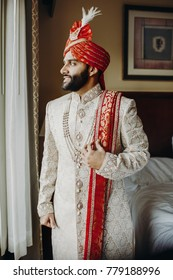 Handsome bearded Indian gromm dressed in rich white Sherwani, decorated with pearls stands before a window