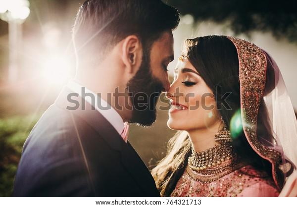 Handsome bearded Indian groom kisses bride in pink dress tender standing outisde
