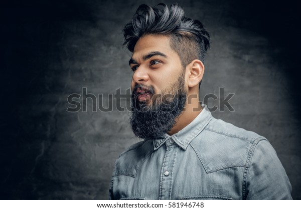 A handsome bearded Indian male dressed in a fleece shirt over grey vignette background.