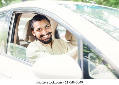 Handsome bearded indian man in kurta driving a car