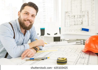 Handsome bearded male architect working on a building plan at his desk smiling to the camera joyfully copyspace professionalism trustworthy qualified experienced engineer constructionist developer