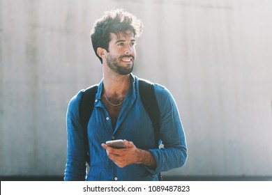Handsome bearded male blogger wearing stylish clothes writing article for publication on personal website by mobile phone connected to internet. Young hipster guy chatting in cosial network outdoors