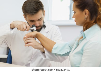 Handsome bearded male dermatologist examining his female patient checking her birthmarks and moles using dermatoscope professionalism device technology modern medicine checkup healthcare dermatology