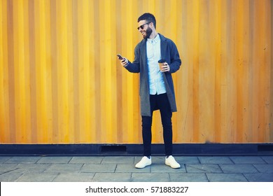 Handsome bearded male hipster making photo for blog sharing positive emotions feeling excited by sunny morning while walking to work with cup of coffee using modern smartphone and 4G internet