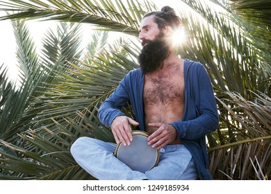 Handsome bearded male playing on darbuka sitting in palm tree leaves and sun in background