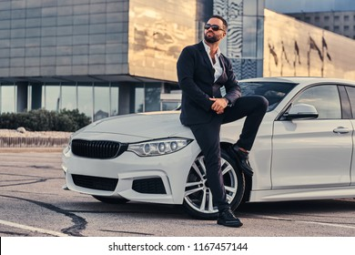 Handsome bearded male in sunglasses dressed in a black suit sitting on luxury car against a skyscraper.