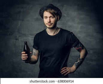 Handsome bearded male with tattooed arms, dressed in a black t shirt and top hat holds craft bottled beer.