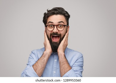 Handsome bearded male in trendy glasses keeping hands near face and shouting in amazement while standing on gray background and looking at camera