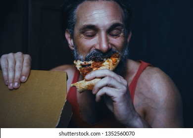 Handsome Bearded Man Bites A Big Piece Of Pizza. Happy Face Of Satistified Man Biting A Piece Of Pizza. Hungry Man Eats Delivered Pizza. Portrait. Closeup. Eating Pizza Concept