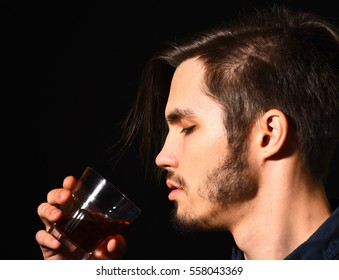 handsome bearded man in blue shirt with stylish hair on serious face holding and drink whisky in black studio background, close up