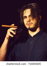 handsome bearded man in blue shirt with stylish hair on serious face holding cigar and whisky in black studio background