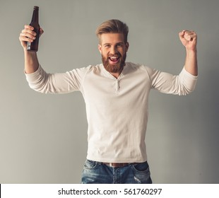 Handsome bearded man in casual clothes is holding a bottle of beverage and cheering, on gray background