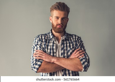 Handsome bearded man in casual clothes is looking at camera while standing with folded arms on gray background