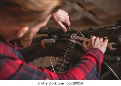 Handsome bearded man in casual clothes is using a spanner while repairing a motorcycle in the repair shop