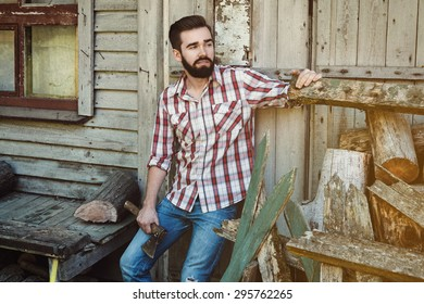 Handsome bearded man in checkered shirt with axe
