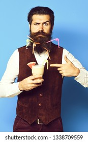 handsome bearded man with colorful tubes in long beard and mustache has stylish hair on serious face holding glass of alcoholic cocktail in vintage suede leather waistcoat on blue studio background.