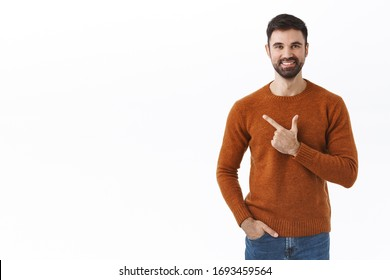 Handsome bearded man, company owner inviting support his start-up, pointing finger left, showing info or product banner advertisement, smiling pleased, recommend click and find out