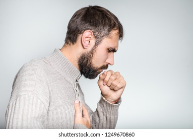 handsome bearded man coughing, closeup over background