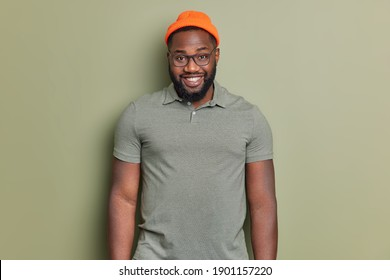 Handsome bearded man with dark skin feels happy wears orange hat and t shirt isolated over khaki background. Afro American guy has cheerful expression smiles broadly poses indoor. Emotions concept