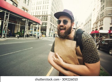 Handsome bearded man doing shopping on Manhattan, New York City having fun laughing outside in streets of New York in summer day. Male person makes funny faces and laughs holding a shopping bag.