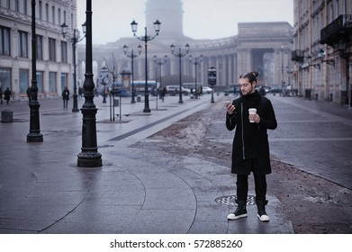 Handsome bearded man drinking coffee on the street and using his smart phone