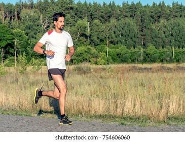 A handsome bearded man is engaged in jogging. Running along the asphalt outside the city. Healthy lifestyle. Running through the sunset.