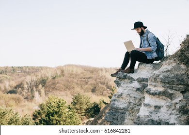 handsome bearded man freelancer working on a laptop outdoors in mountains. Freelance concept