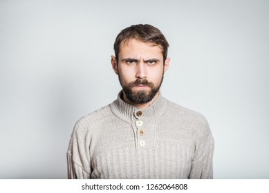 handsome bearded man frowned and angry, close-up over background