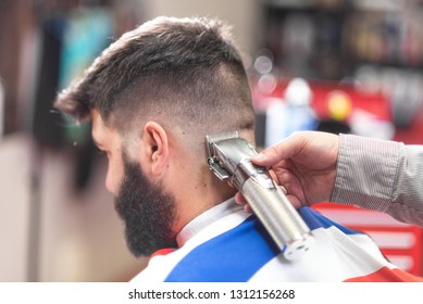 Handsome bearded man, getting haircut by barber, with electric trimmer at barbershop .