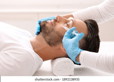 Handsome bearded man getting nasolabial folds filler at aesthetic clinic, side view. Plastic surgeon hands in blue gloves making beauty injection for wealthy attractive middle aged man