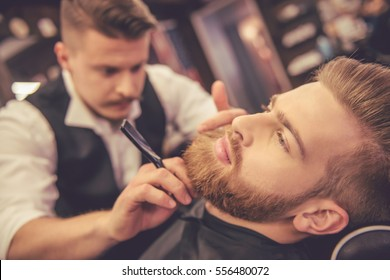 Handsome bearded man is getting shaved by hairdresser at the barbershop