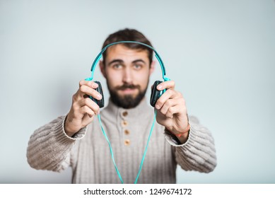 handsome bearded man gives listen to music in big headphones, close-up over background