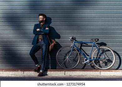 handsome bearded man in glasses and cap posing near bicycle