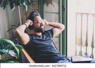 Handsome bearded man in headphones enjoy listening to music at home. Relaxing and rest time concept. Blurred background.