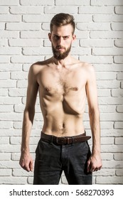 handsome bearded man or hipster guy dieting with bare slim or thin body, chest and torso with anorexia on white brick wall background