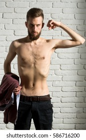handsome bearded man or hipster guy dieting with bare slim or thin body, chest and torso with anorexia holds purple shirt on white brick wall background