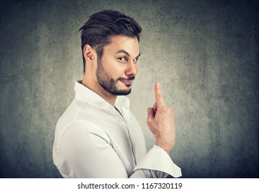 Handsome bearded man holding finger up for number one being ironic on gray background