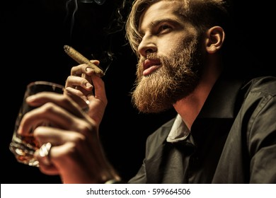 Handsome bearded man holding glass of whisky and smoking cigar isolated on black