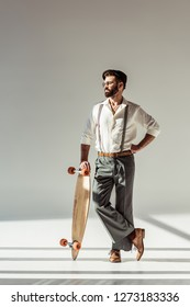 handsome bearded man holding longboard on grey background