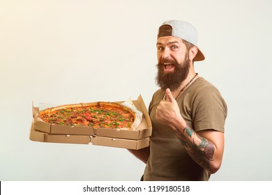 Handsome bearded man holding pizza very happy pointing with hand and finger.