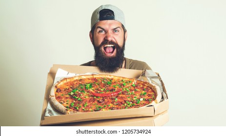 Handsome bearded man holding pizza very happy pointing with hand and finger. Young handsome pizza delivery man holding pizza boxes isolated over grey background. Food delivery home.