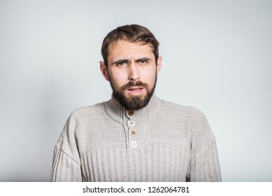 handsome bearded man is indignant; closeup over background