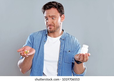 Handsome bearded man isolated on a white background with a bottle of pills.  Guy holds a hand full of pills. He is concerned about expensive medicine but he wants to be healthy again.
