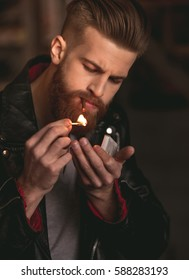 Handsome bearded man in leather jacket is lighting up a cigarette