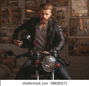 Handsome bearded man in leather jacket is holding a helmet and looking at camera while sitting on the motorcycle in the repair shop