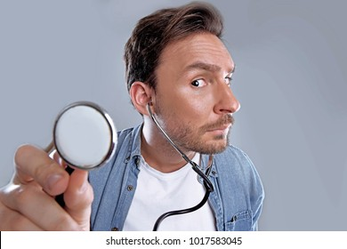 Handsome bearded man lisening to stethoscope, Funny Guy with big nose in a white t shirt and blue short is concerned about his health is worried and scared