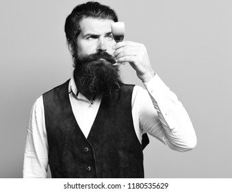 handsome bearded man with long beard and mustache on serious face tasting glass of alcoholic shot in vintage suede leather waistcoat on blue studio background