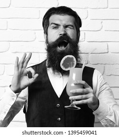 handsome bearded man with long beard and mustache has stylish hair on funny face holding glass of alcoholic beverage in vintage suede leather waistcoat on white brick wall studio background.